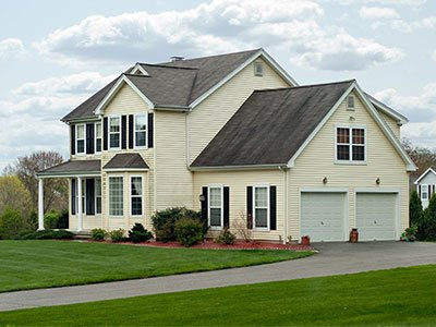 suburban house with light yellow siding and landscape