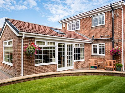 suburban house with brick and big white windows and lanscape