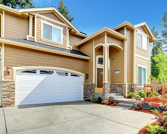 suburban house withlight brown siding,big white garage door and paved alleyway