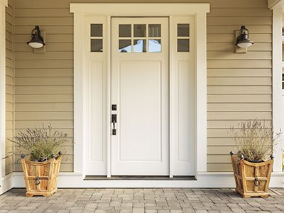 closeup of front white door in suburban house, with plants at the entrance