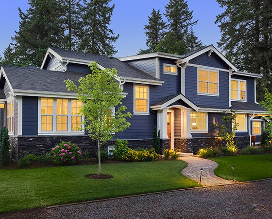suburban house with blue siding, landscape, and interior lights on