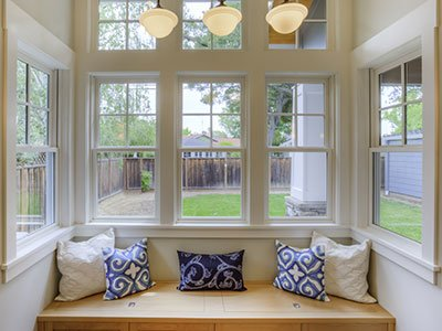 closeup of a window looking outside, with cozy bench with pillows