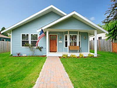suburban small house with green yard, blue siding, white columns and american flag